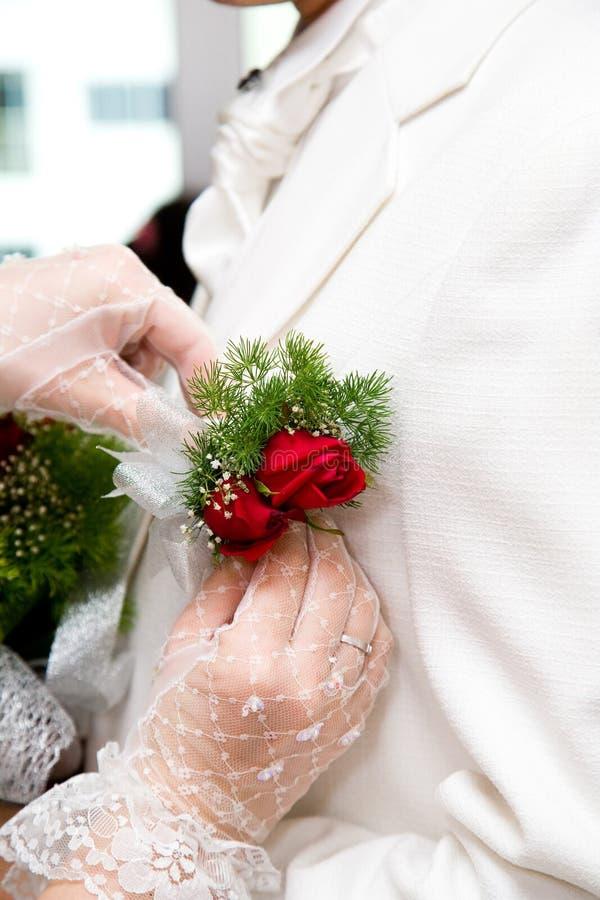 Crochet de rose de rouge mis par mariée à la couche de mariés images stock