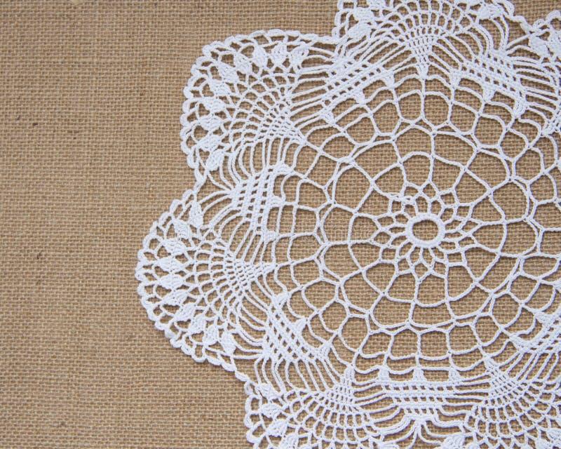 Crochet doily over burlap royalty free stock photography