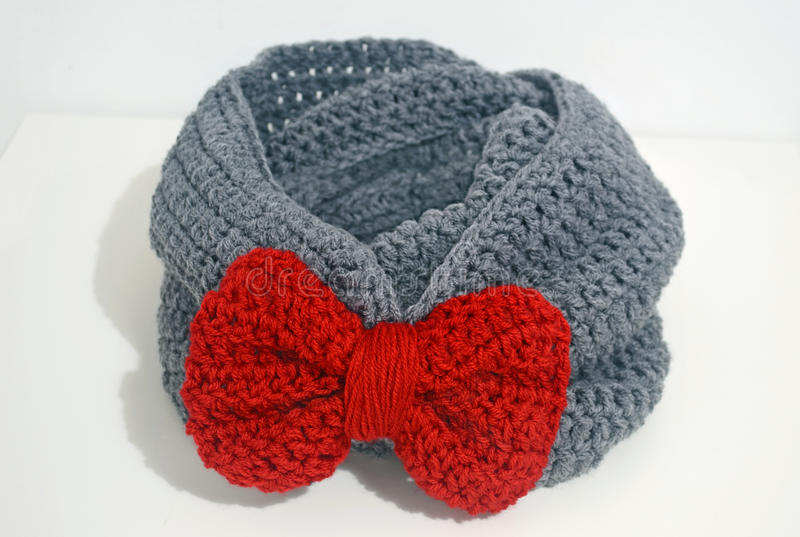 Crochet grey infinity scarf with red bow. Still life of a crochet grey infinity scarf with red bow royalty free stock photos