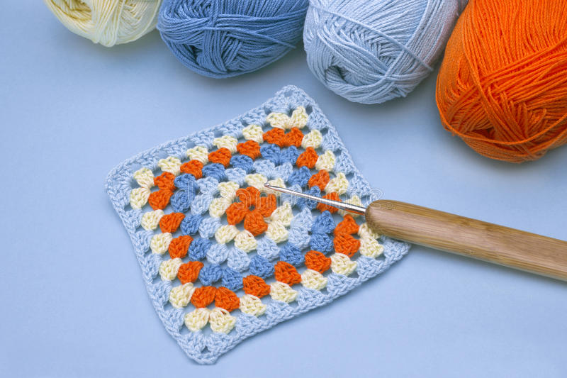 Crochet handmade granny square, a hook and yarn balls. stock image