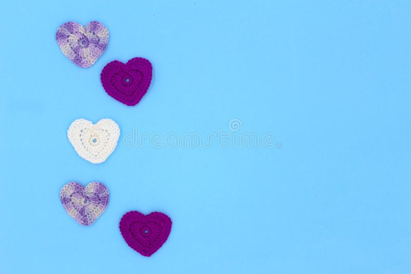 Crochet hearts on a blue backing. St. Valentine`s Day stock photography