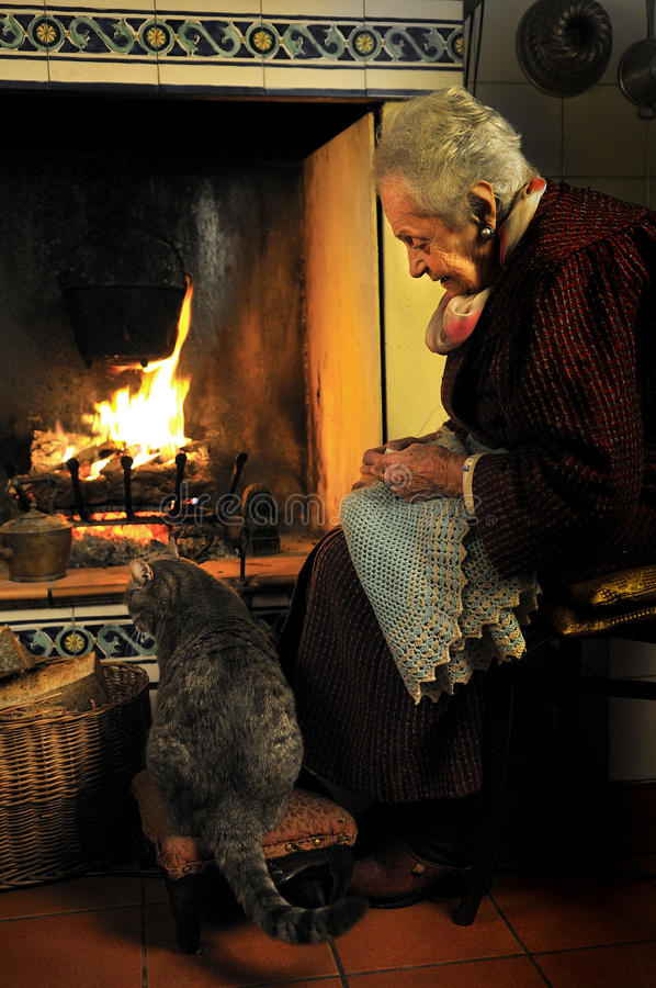 Crochet hook. An old women and her cat in front of the fireplace stock photography
