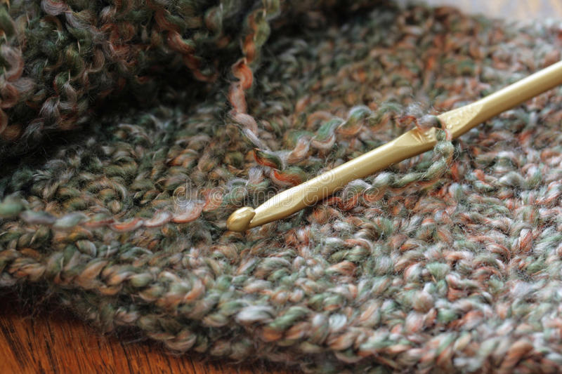 Crochet Hook and Yarn. A closeup of a skein of sage green acrylic yarn with a crochet hook resting on a double crocheted scarf royalty free stock photos