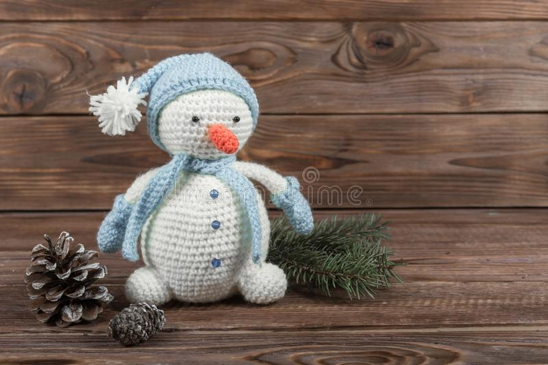 Crochet kraft toy. White snowman in a blue hat and scarf on a dark wooden background. New Year`s gifts stock photo