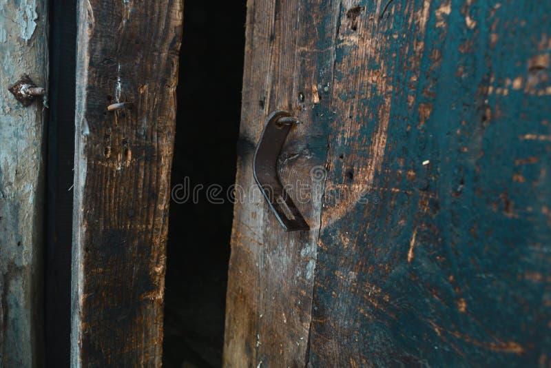 Crochet ouvert rouillé sur la vieille porte en bois, fond brun Place pour le texte photos libres de droits