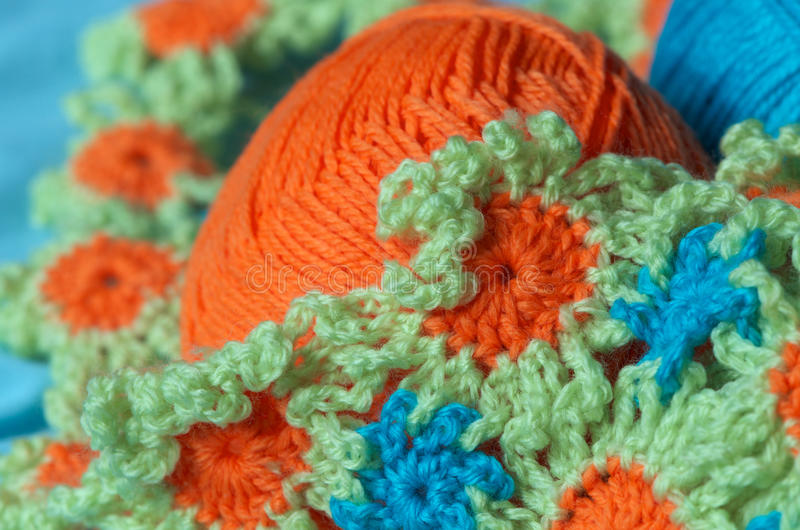 Crochet pattern. Cute crochet project; flower pattern with wool of three bright spring colours (green, blue, orange royalty free stock image