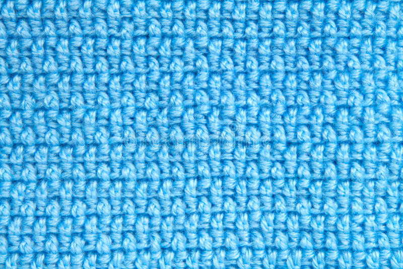 Crochet yarn pattern blanket blue background. Baby blanket close up on crochet pattern alternating front loop double crochet with back loop double crochet stock photo
