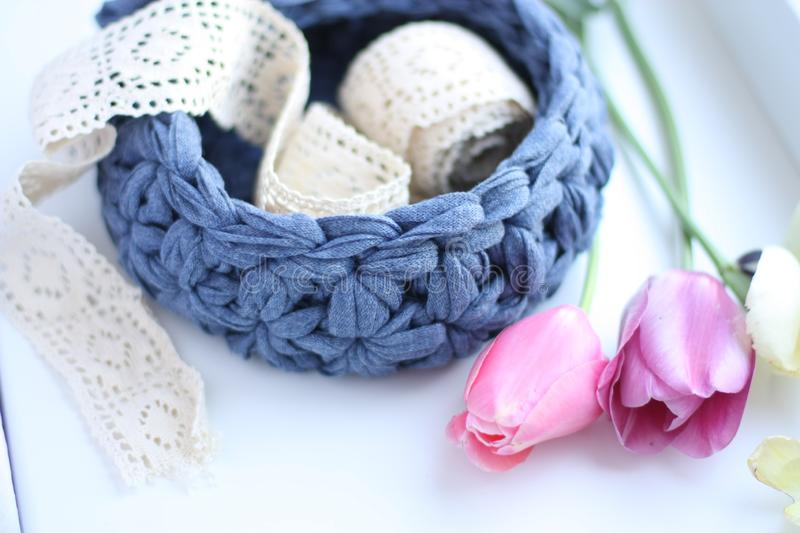 A crocheted basket with lace and tulips. On white background royalty free stock image