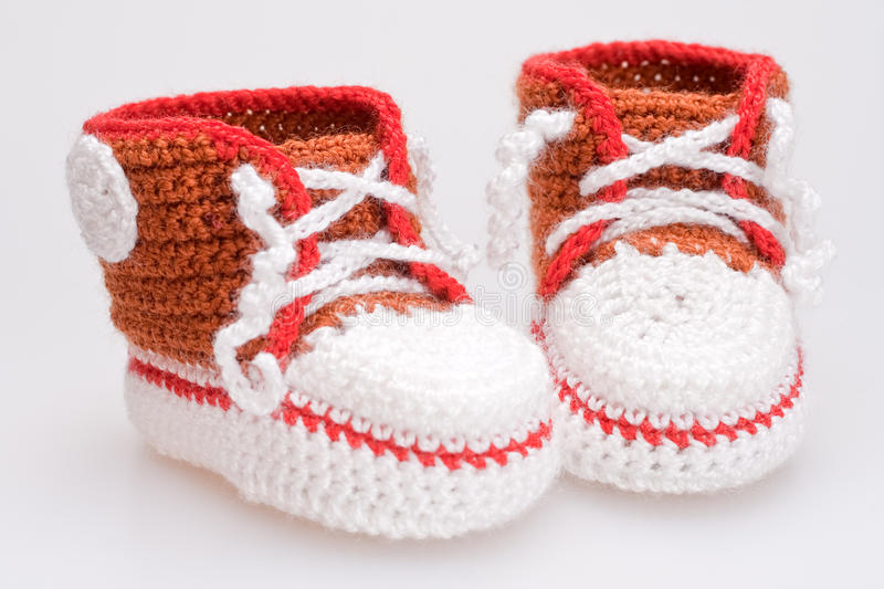 Crocheted booties for a boy. On a gray background royalty free stock photography