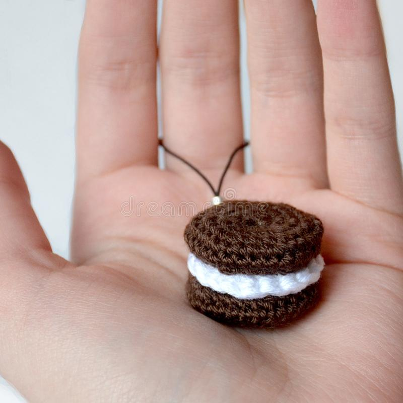 Crocheted brown cookies with a layer of white cream. Keychain on. Hand royalty free stock photography