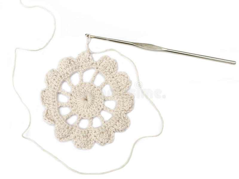 Crocheted flower. And crochet needle, isolated on white royalty free stock photography
