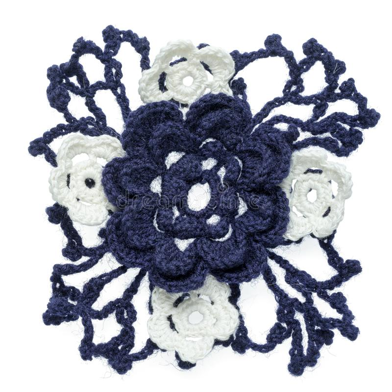 Crocheted flower. One blue crocheted big flower element with net of leaves and small white flowers as a bouquet element isolated on white background royalty free stock image