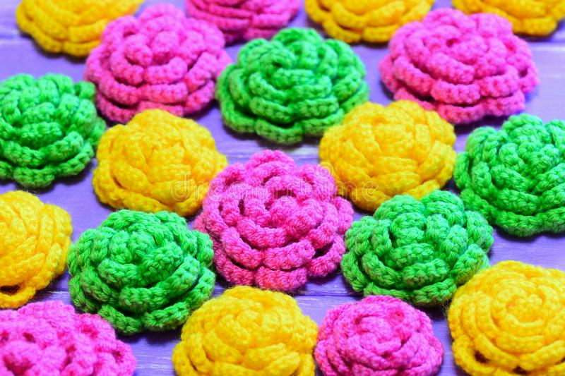 Crocheted flowers. Yellow, pink and green crocheted flowers. Multicolored floral ornaments. Bright background. Closeup stock photography