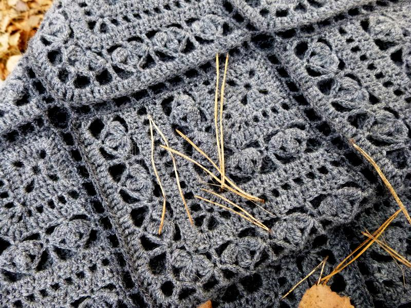 Crocheted gray shawl. Square motifs, fringe. Autumn leaves and needles of pine fell from above royalty free stock images