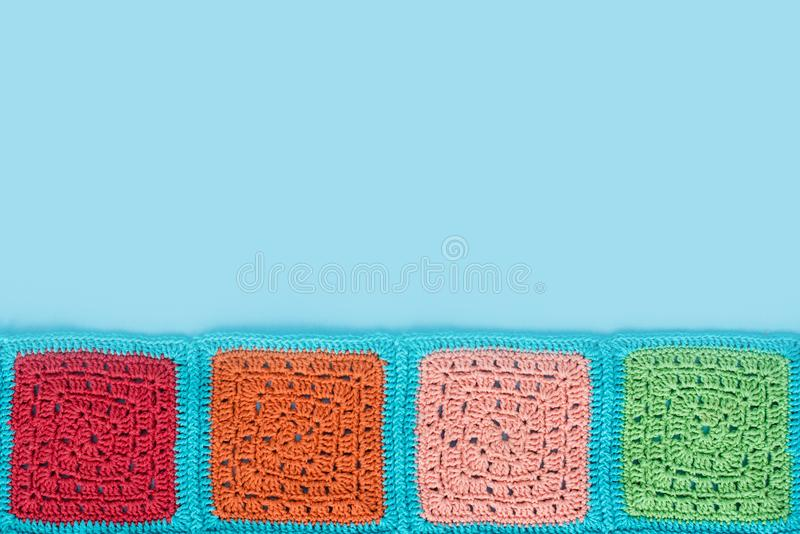 Crocheted lace tablecloth of multicolored squares ornament on a blu background, top view, place for text, natural wool.  stock photo