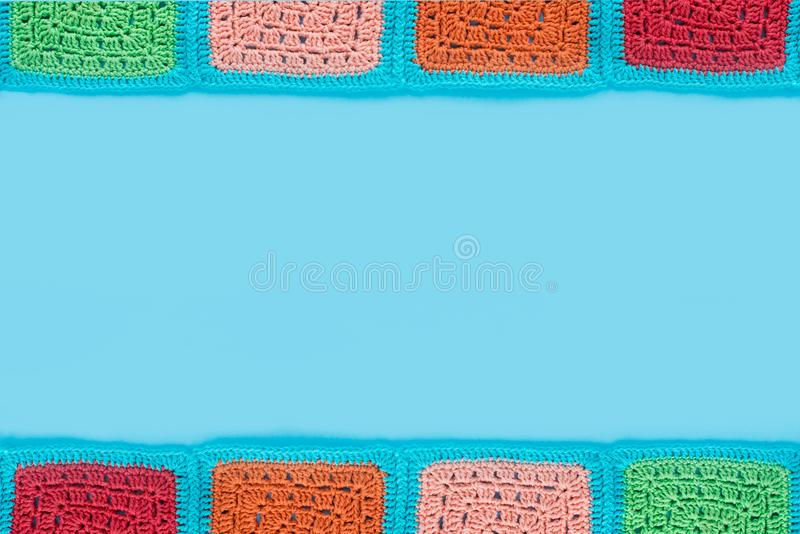 Crocheted lace tablecloth of multicolored squares ornament on a blu background, top view, place for text, natural wool.  stock photography
