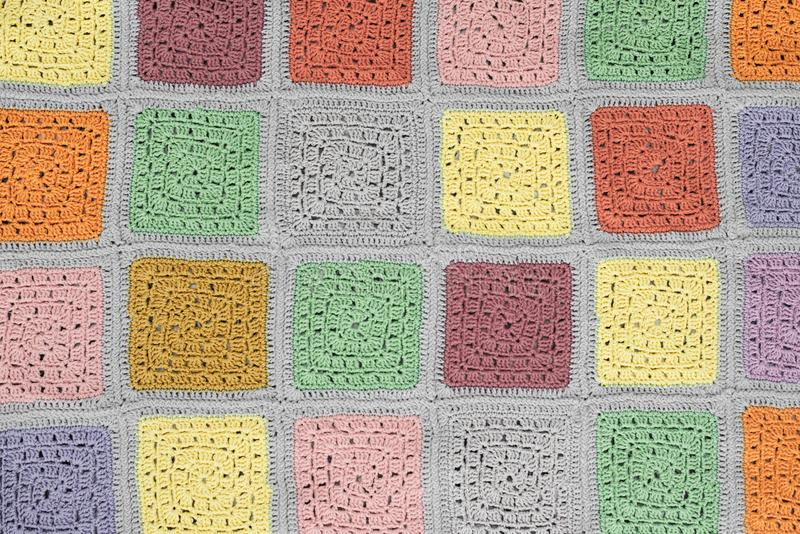 Crocheted  lace tablecloth of multicolored squares ornament on a gray background, top view, place for text, natural wool.  stock photo