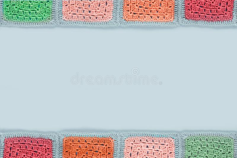 Crocheted lace tablecloth of multicolored squares ornament on a gray background, top view, place for text, natural wool. Grandma crocheted lace tablecloth of stock photo