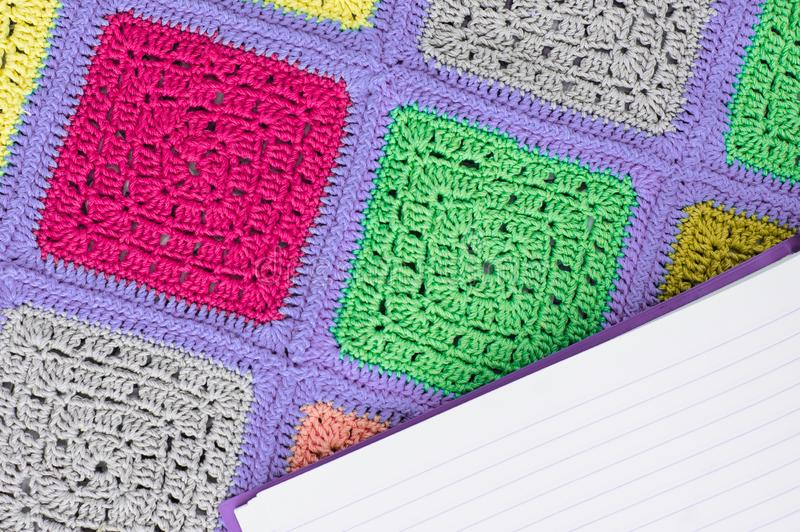 Crocheted  lace tablecloth of multicolored squares ornament, sheet of notebook to write to the ruler, top view,. Place for text, natural wool stock photo