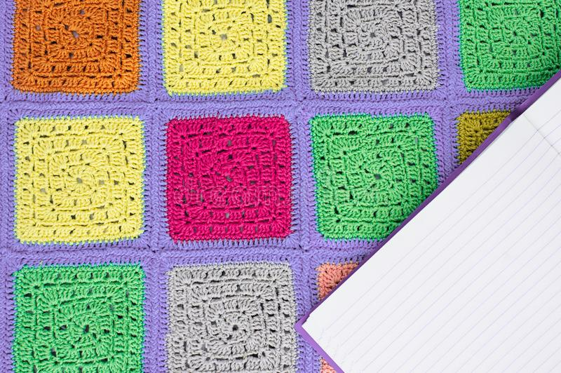 Crocheted  lace tablecloth of multicolored squares ornament, sheet of notebook , top view, place for text, natural wool. Crocheted  lace tablecloth of royalty free stock photography