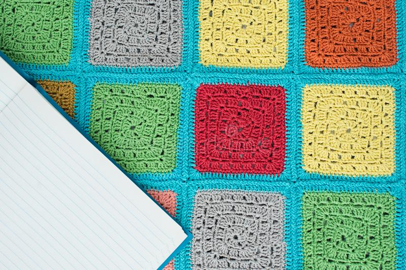 Crocheted  lace tablecloth of multicolored squares ornament, sheet of notebook, top view, place for text, natural wool. Crocheted  lace tablecloth of stock image