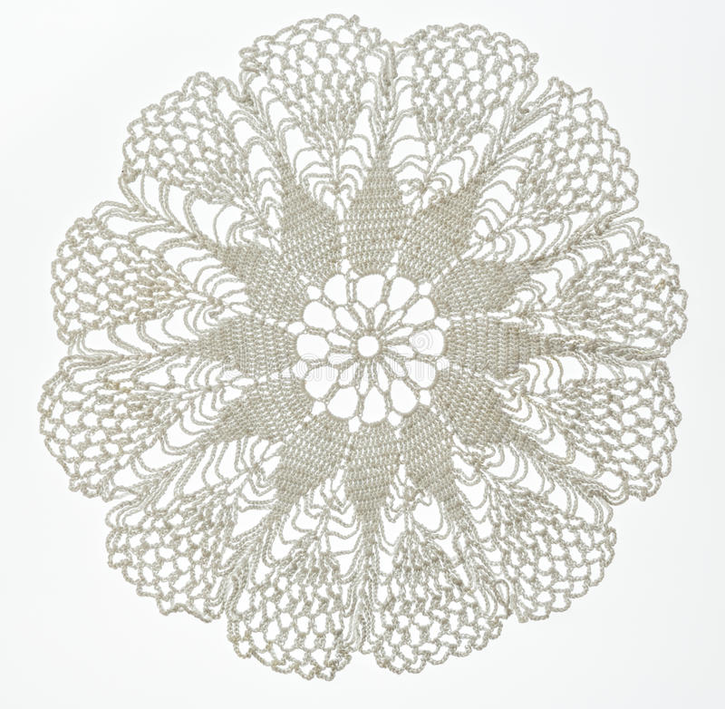 Crocheted lace on white. Crocheted lace napkin as home decoration on white stock photo