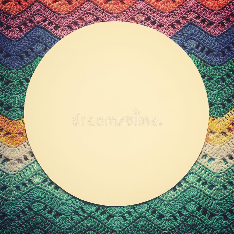 Crocheted multicolored cotton canvas. Round white frame for text stock photo