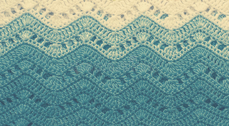 Crocheted multicolored cotton fabric In blue colors. Striped wavy structure or background. Vintage toning royalty free stock photo
