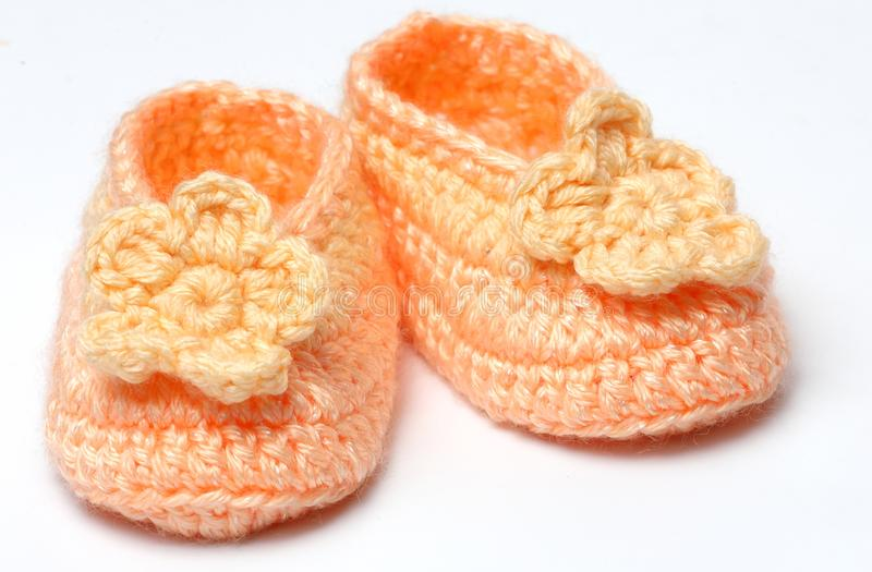 Knitted crochet shoes baby newborn. Crocheted natural wool colored newborn baby shoes on white background royalty free stock photo