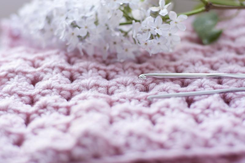 Crocheted pattern with lilac flowers and hooks royalty free stock image