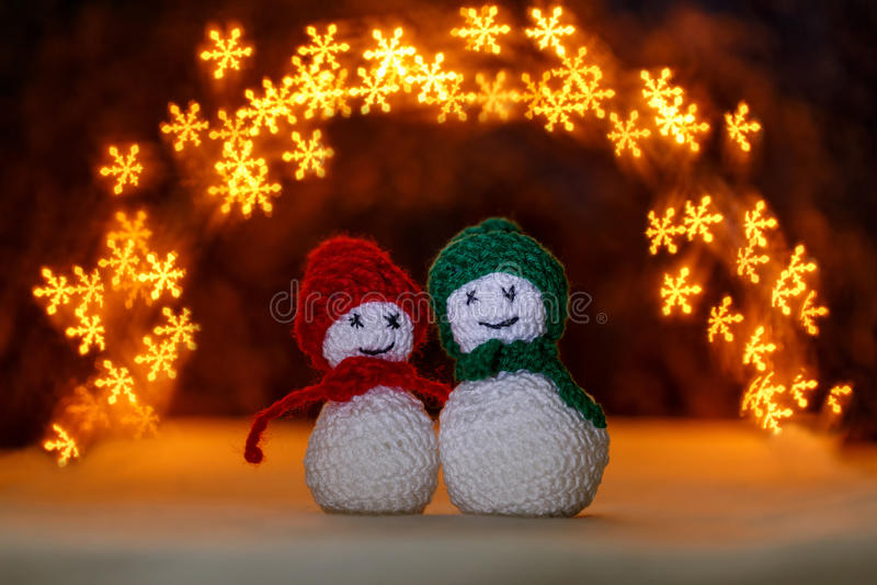 Crocheted snowmens and bokeh like snowflakes stock photo