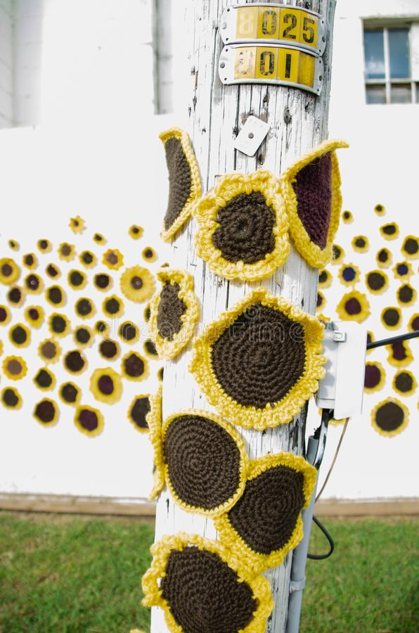 Crocheted sunflowers on a pole with additional flowers in the background. stock images