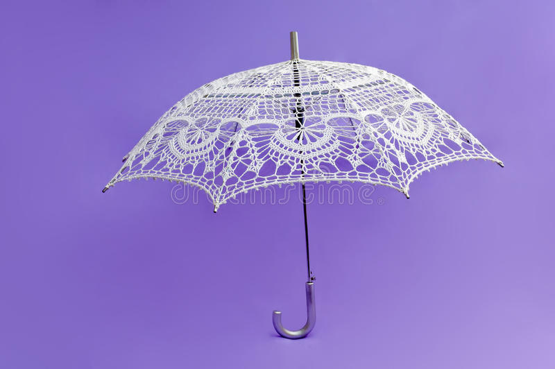 Crocheted white umbrella. On violete background royalty free stock image
