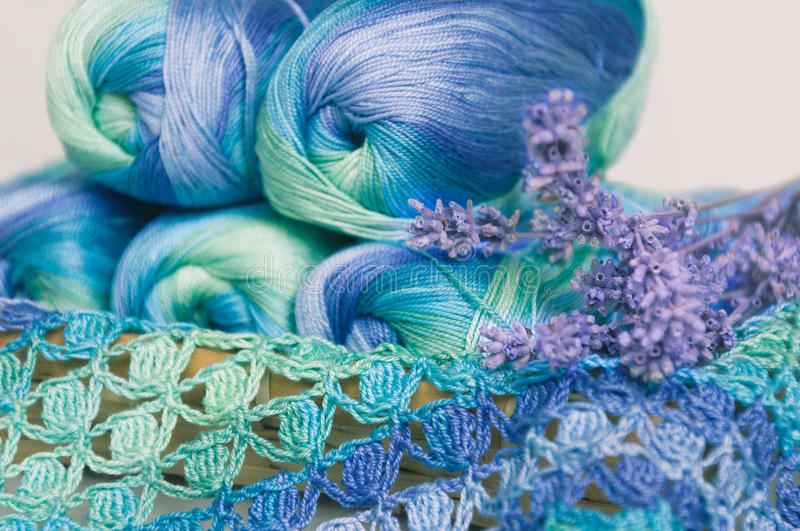Crocheting in blue and green tones and skeins piled together stock image