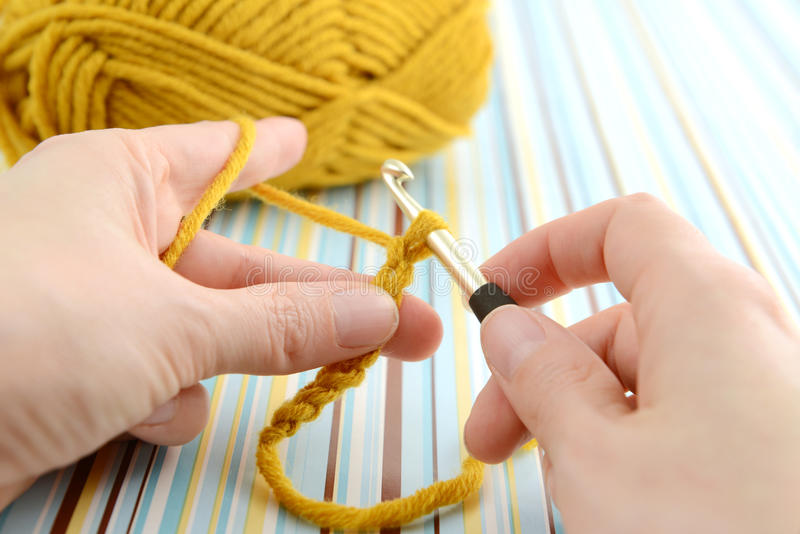 Crocheting with brown wool in hand. stock photos