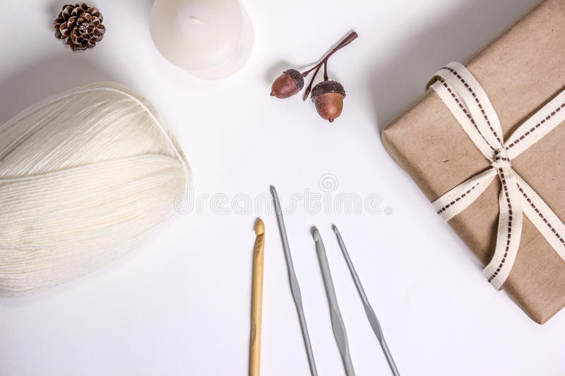 Crocheting supplies, hooks and white yarn, mailing box decorated with ribbons and some natural decorations. Background for hobby presentations stock photos