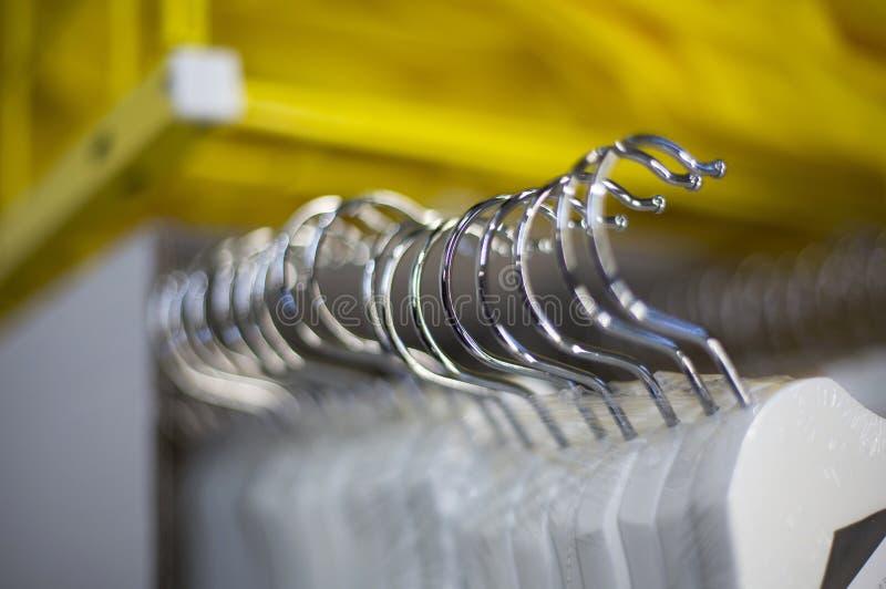 Crochets brillants en acier d'un plan rapproché de cintre photographie stock libre de droits
