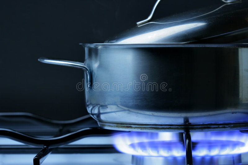 Crock on the gas stove. Over black background royalty free stock photos