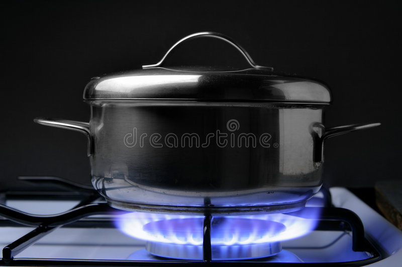 Crock on the gas stove. Over black background royalty free stock images