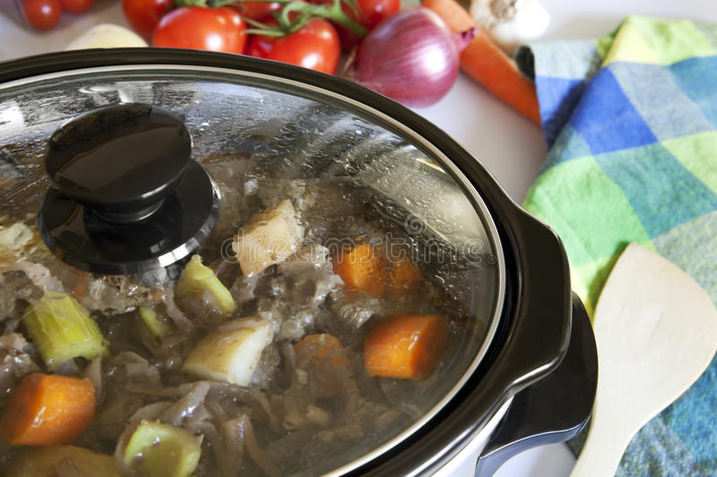 Crock Pot Cooking. A crock pot slow-cooking a homely beef casserole stock images