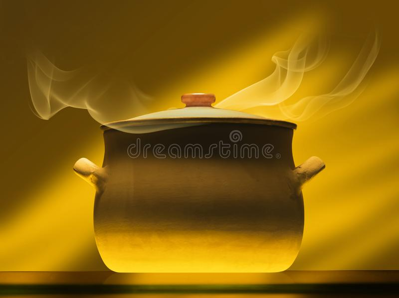 Crock pot on mirror plate. With steam, warm light royalty free stock photos