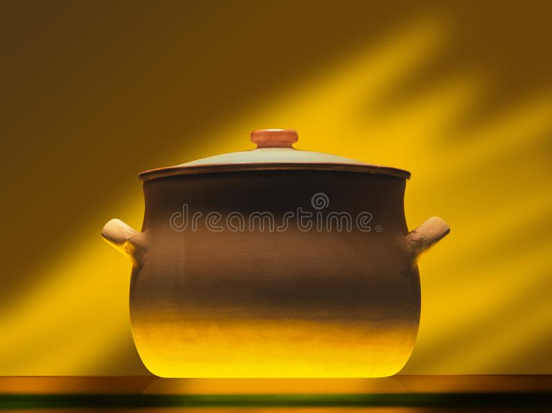 Crock pot on mirror plate. Without steam, warm light stock photography