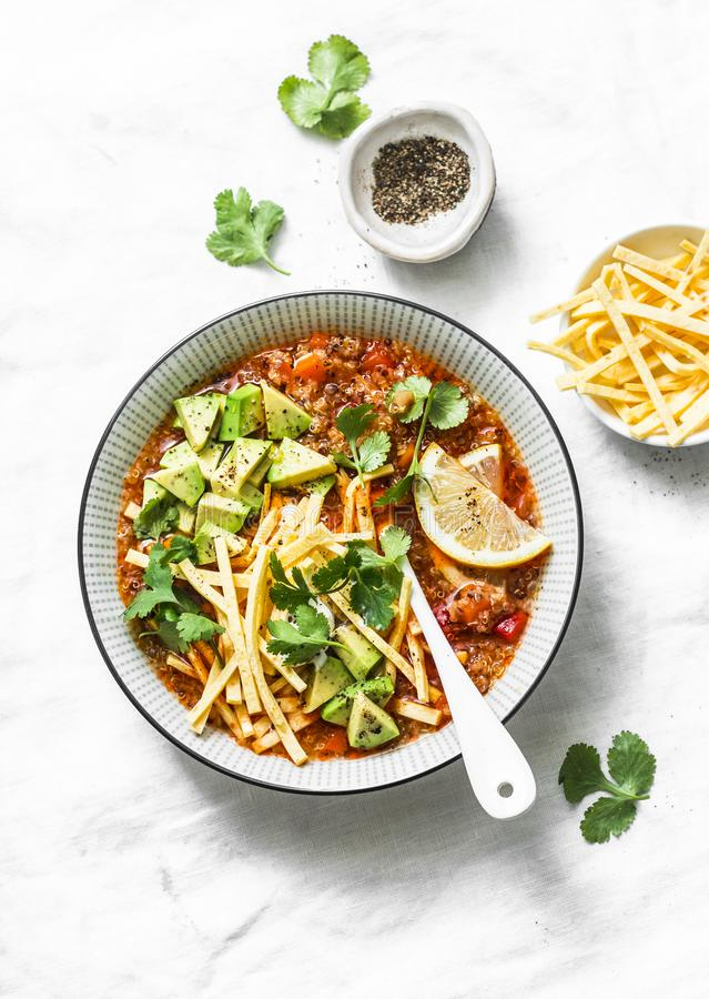 Crock pot vegetarian quinoa tomato soup with corn tortilla chips, avocado and cilantro on light background. Top view stock images