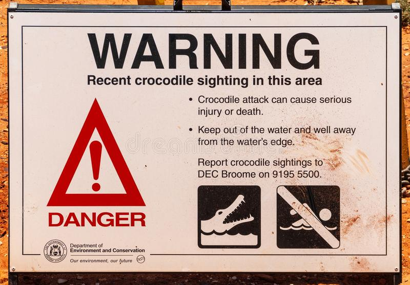 Crocodile warning sign in Broome, Australia. Broome, WA, Australia - November 29, 2009: Public display poster by government about the recent sighting of stock photos
