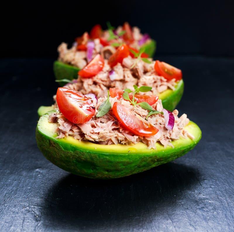 Crogioli di avocado farciti con il tonno, la cipolla rossa ed i pomodori ciliegia fotografie stock