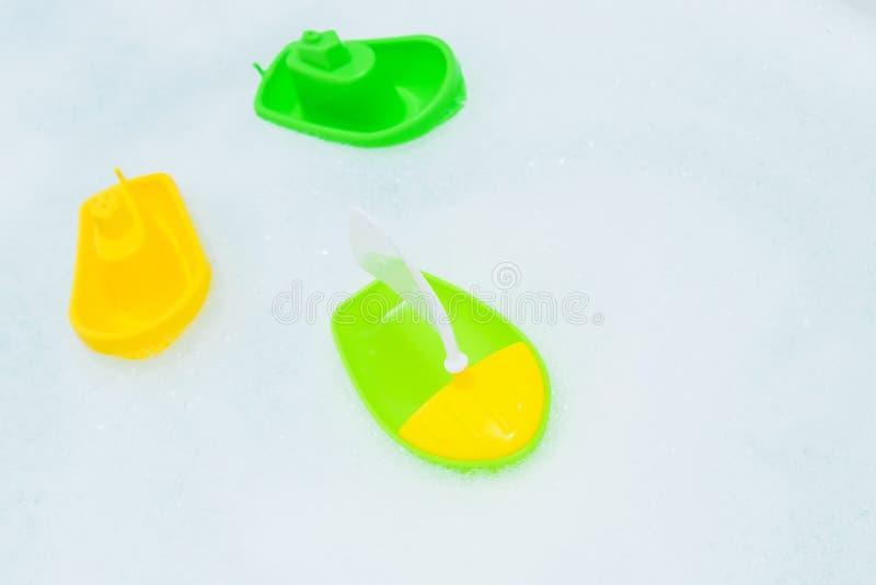 Crogioli multicolori di plastica di giocattolo sulla bagnoschiuma immagini stock