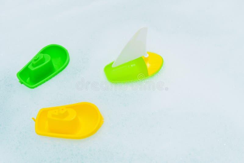 Crogioli multicolori di plastica di giocattolo sulla bagnoschiuma fotografia stock