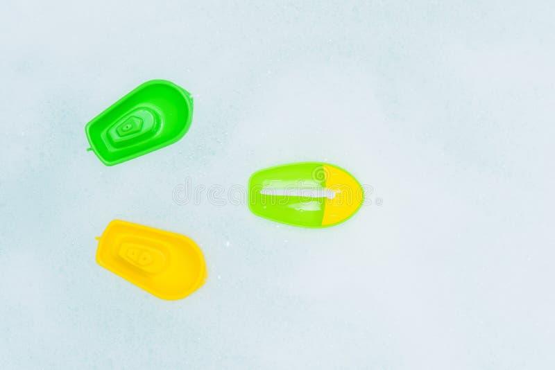 Crogioli multicolori di plastica di giocattolo sulla bagnoschiuma immagine stock
