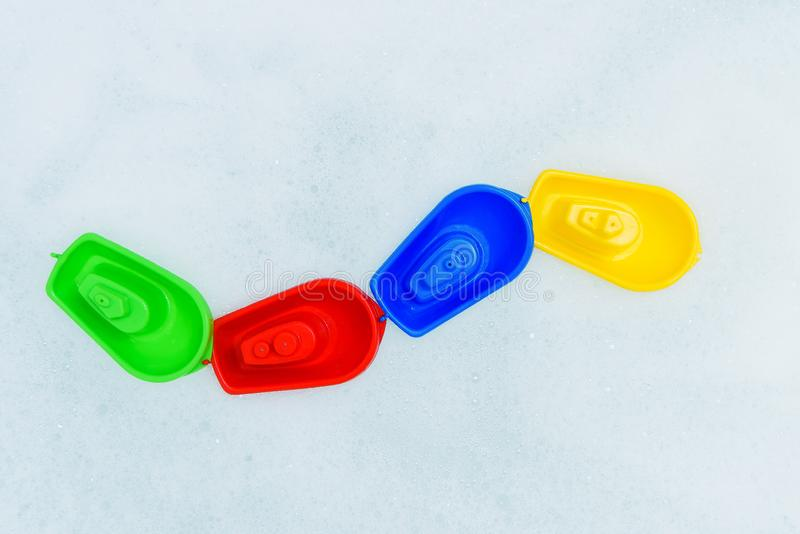 Crogioli multicolori di plastica di giocattolo sulla bagnoschiuma fotografie stock
