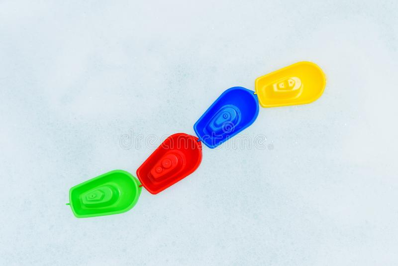Crogioli multicolori di plastica di giocattolo sulla bagnoschiuma fotografia stock libera da diritti